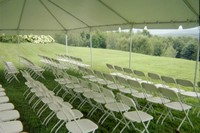 Interior of 20' x 30' frame tent with white samsonite chairs